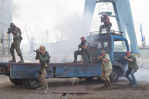 Expendables stand in front of and on top of large truck during gun-fight